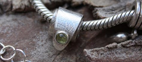 Example of work by students on this course - silver charm set with peridot